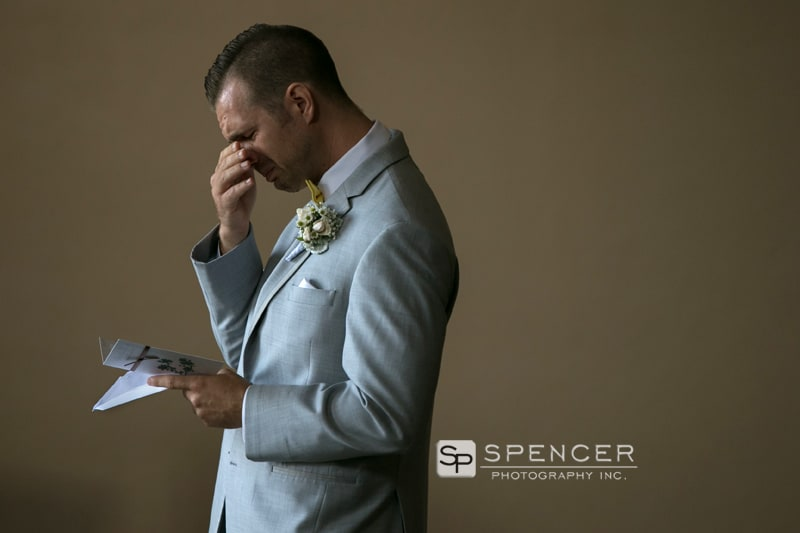 groom reacting to wedding day card from bride