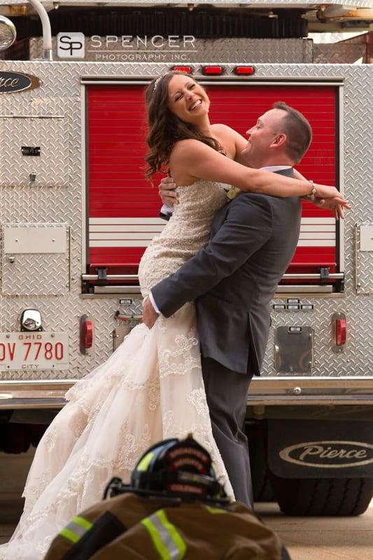 groom lifting bride by firetruck