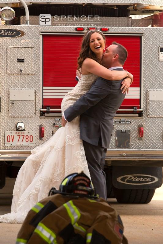 groom kissing bride by firetruck