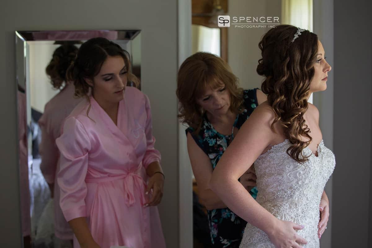 mom helping bride wedding dress