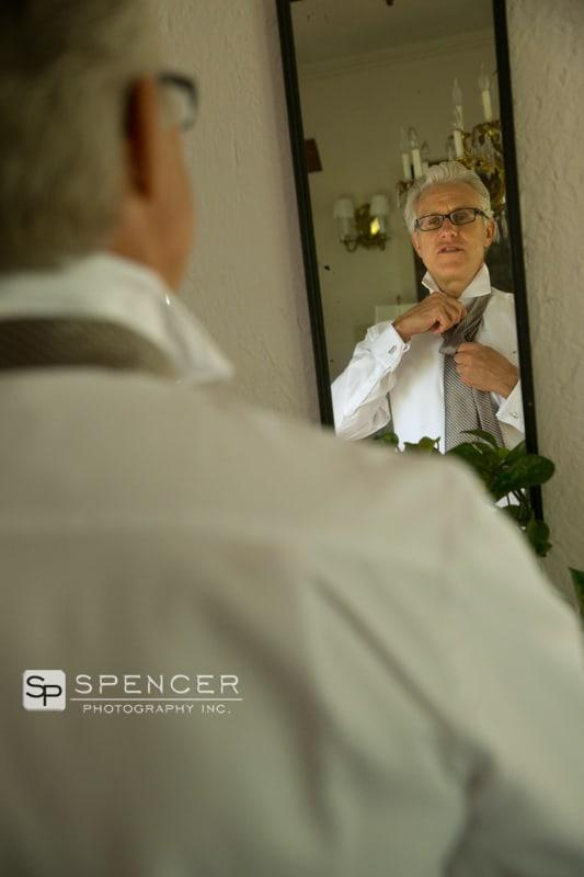 groom adjust tie in mirror