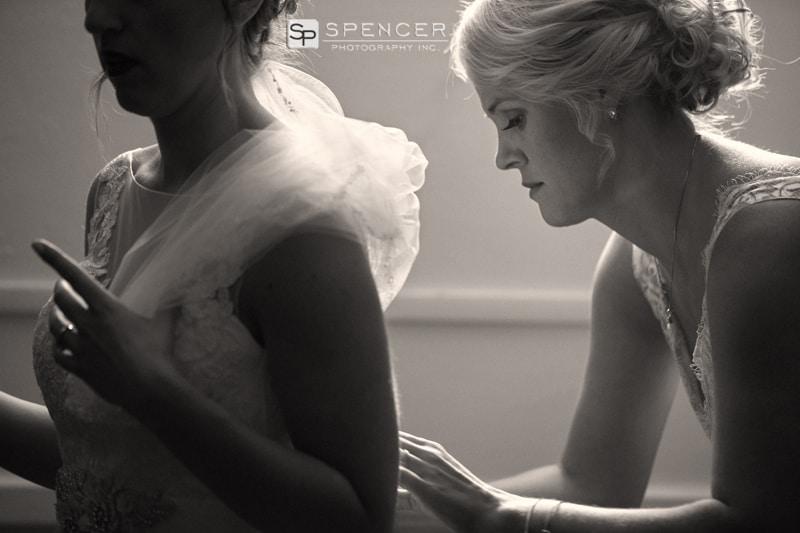 bridesmaid helping bride with wedding dress