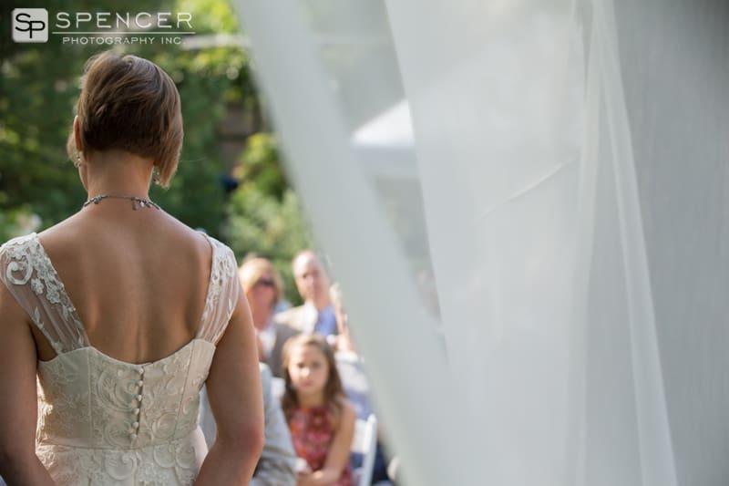 bride at wedding ceremony under arbor
