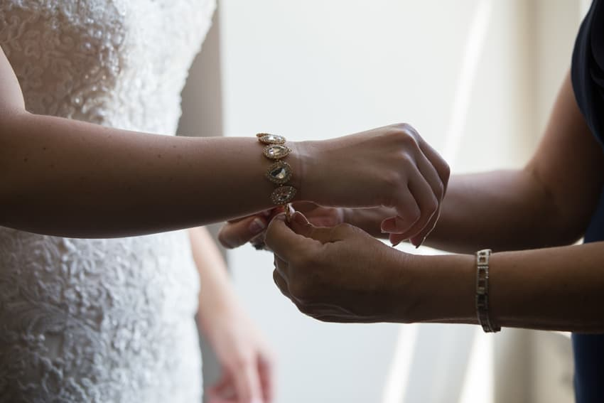 maid of honor helps bride with bracelet