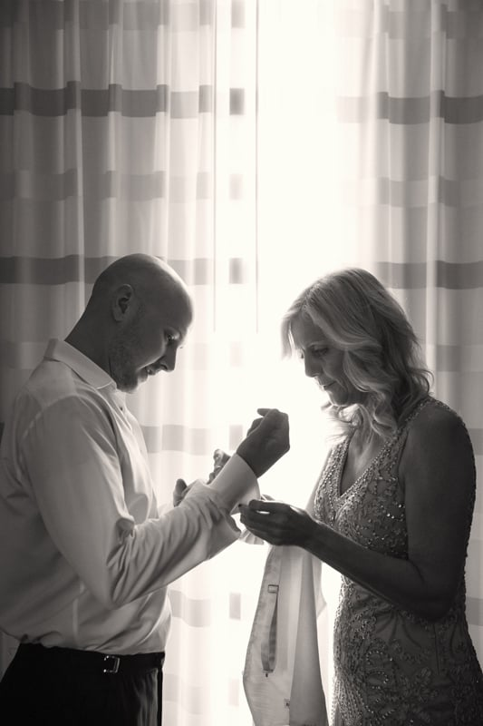 mom helping groom with wedding cuff links