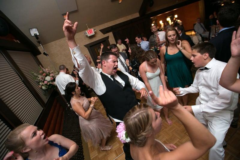groom cheering at his wedding reception