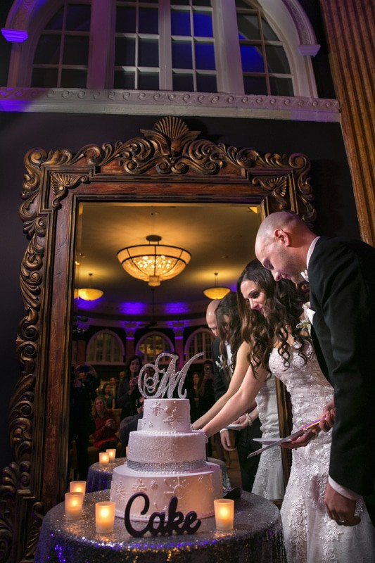 bride and groom cutting wedding cake at reception at ballroom at park lane