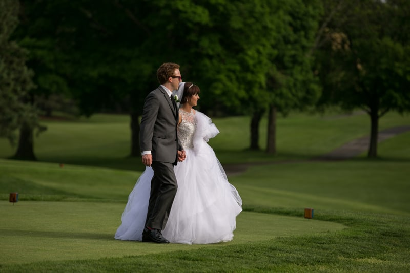 bride and groom walking on greens at firestone country club