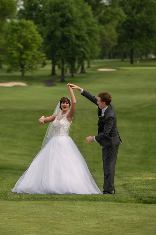 bride and groom dancing on golf greens