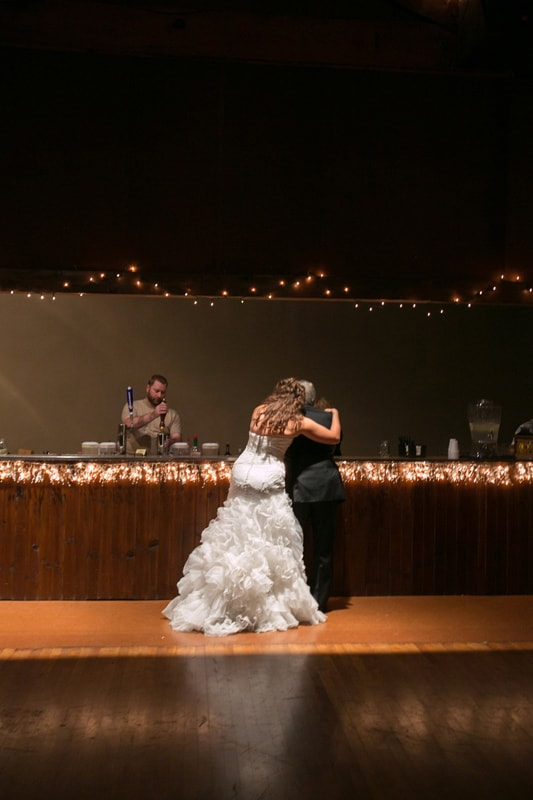 bride hugging guest at bar