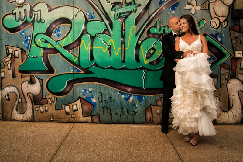 bride and groom picture next to graffiti