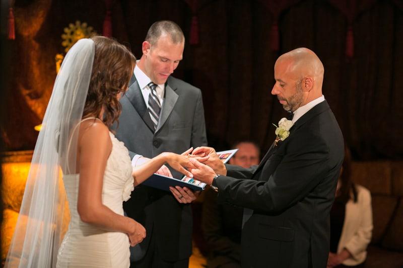 groom putting on wedding band