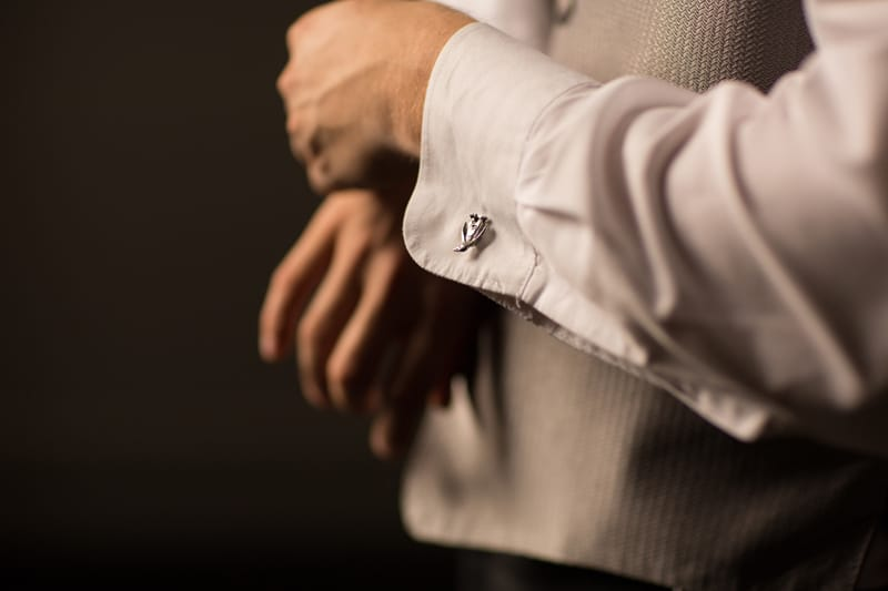 groom putting on cuff links