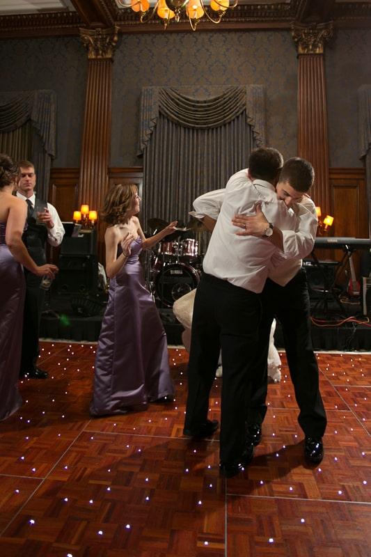 groom hugging groomsmen on dancefloor
