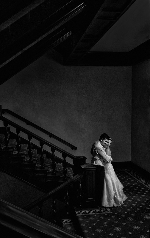 bride and groom hugging on staircase at union club