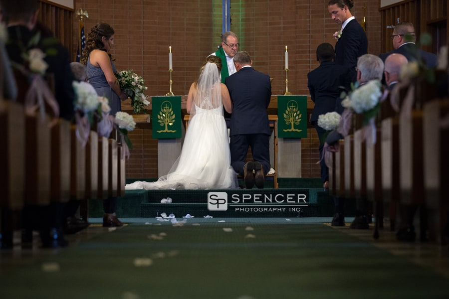 bride and groom kneel during wedding ceremony