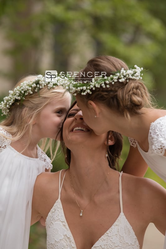 bride getting kissed by flower girls