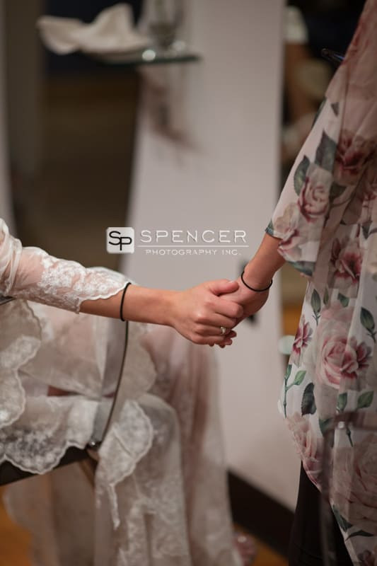 bride holding bridesmaid hand at gravity salon