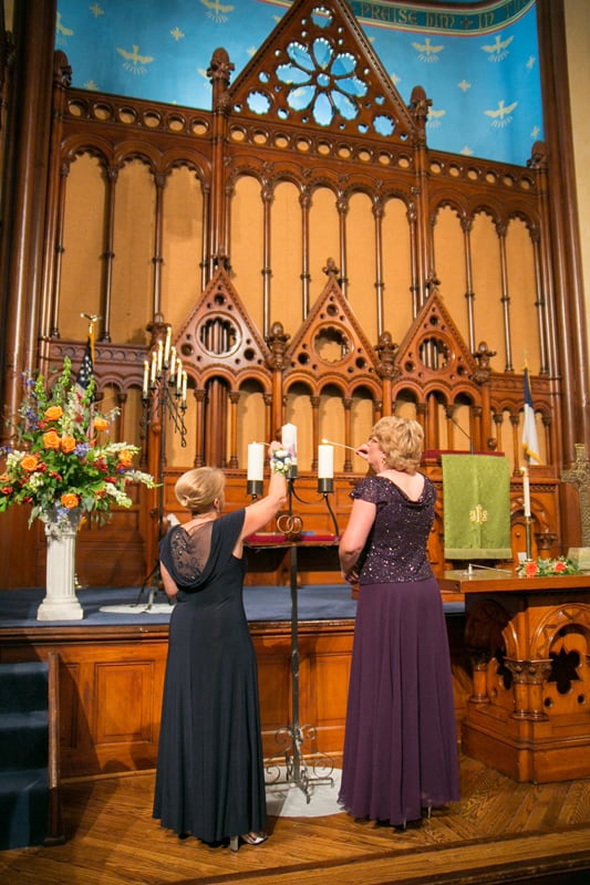 moms lighting wedding candle at old stone church