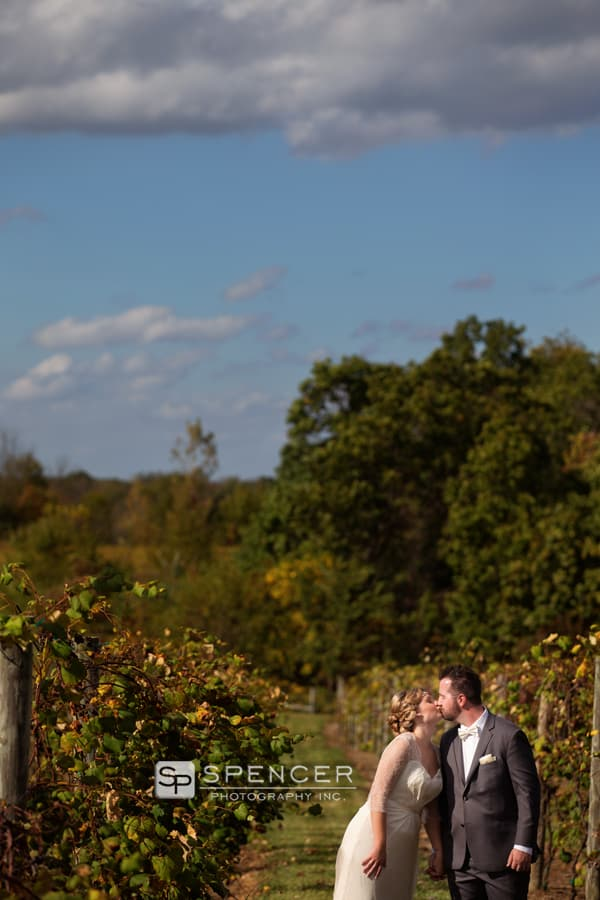 bride and groom kissing in vineyard at breitenbach