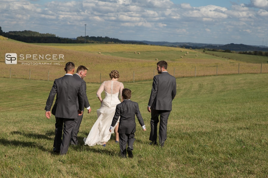 bride walking with groomsmen at breitenbach