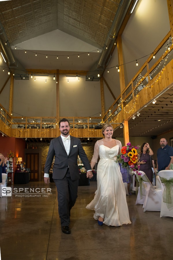 bride and groom entering their reception at breitenbach