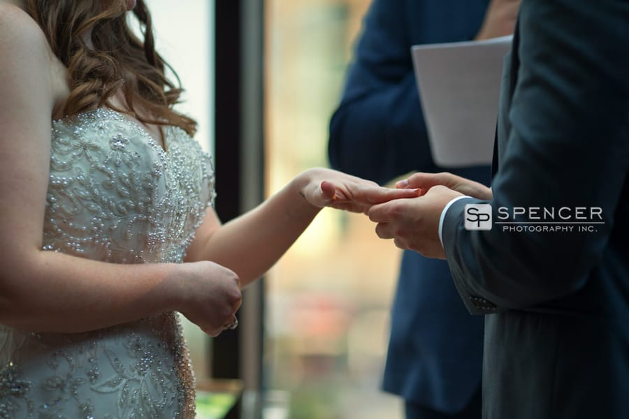 groom putting ring on bride at ceremony at music box supper club