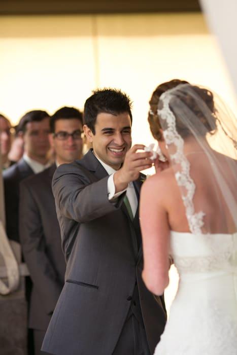 groom wipes away brides tear at ceremony at Gervasi