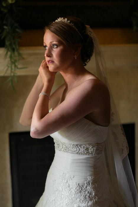 bride putting on her earrings in villa at Gervasi