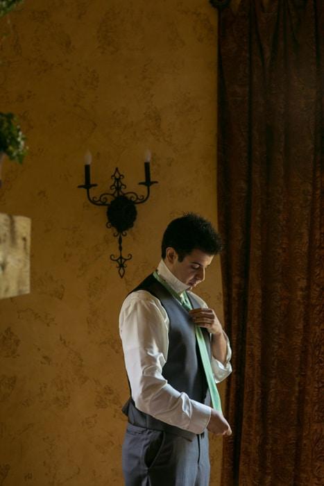 groom getting dressed in villa at Gervasi Vineyard