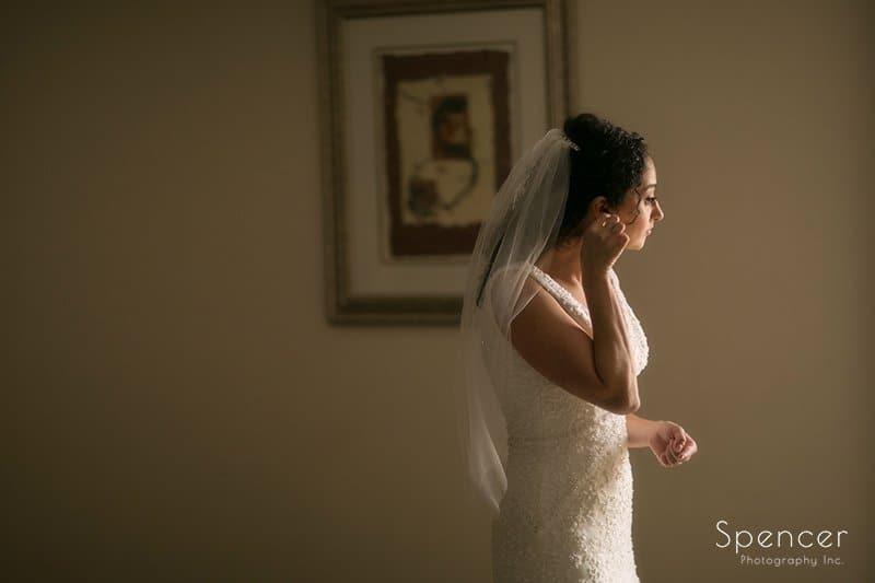 bride adjusting her earring before her wedding in
