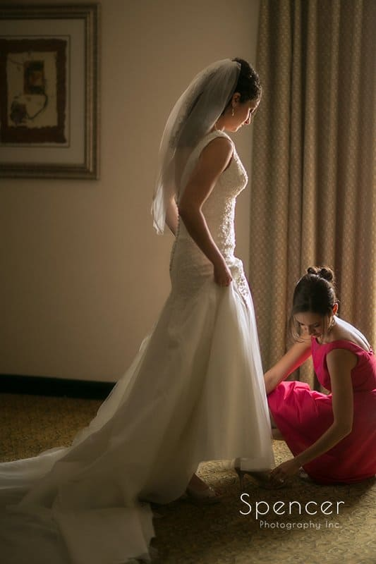 maid of honor helping bride with shoes before her wedding in Tallmadge Ohio