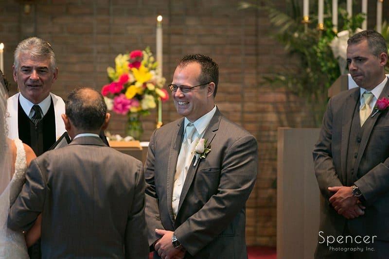 groom smiling at bride walks down aisle