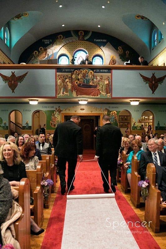 groomsmen pull aisle runner down Greek wedding ceremony in Akron