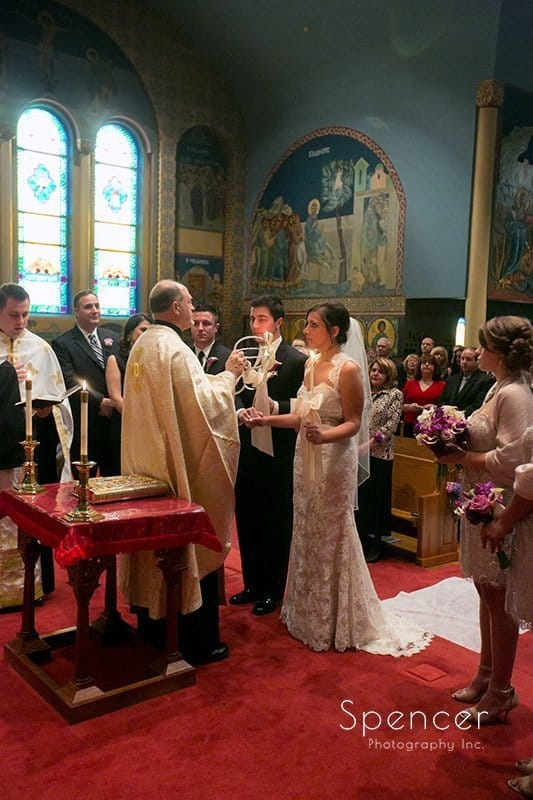 bride and groom stand at altar of their Greek wedding in Akron