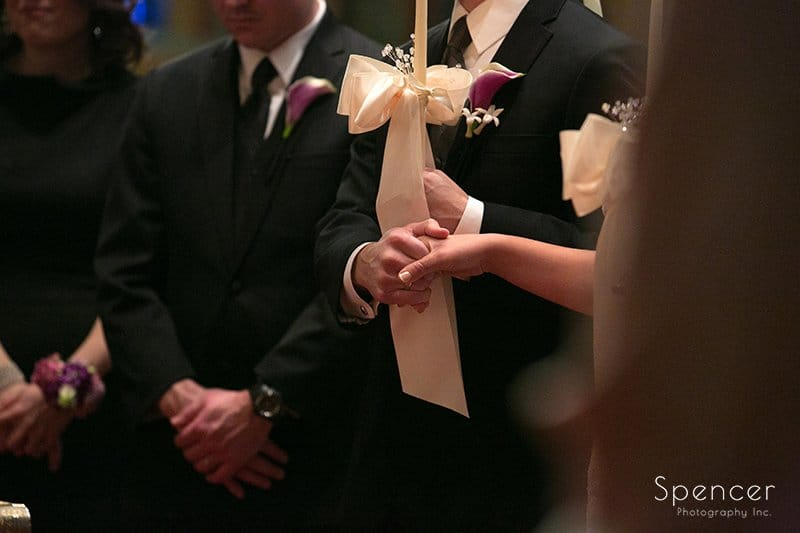 bride and groom hold hands at altar of Greek wedding in Akron