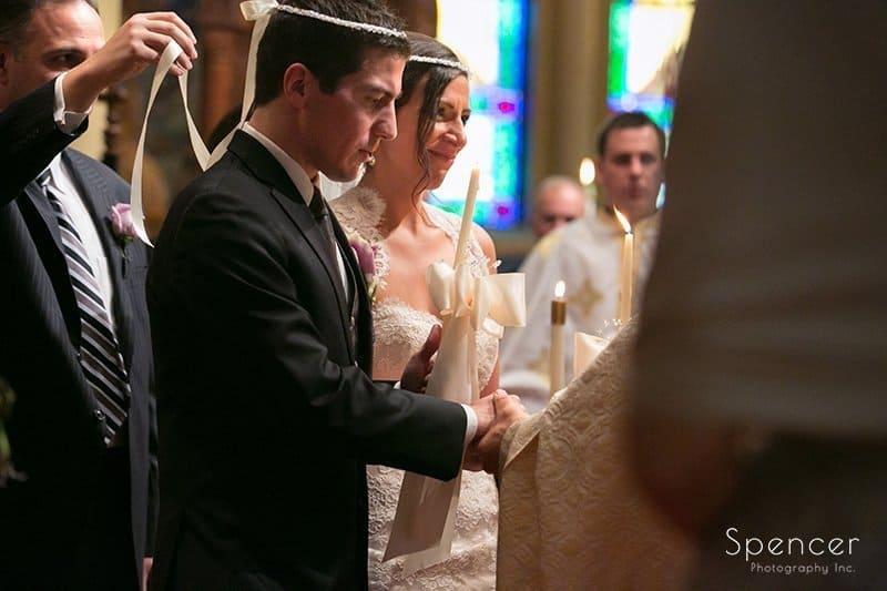 bride and groom walking around altar at Greek wedding in Akron