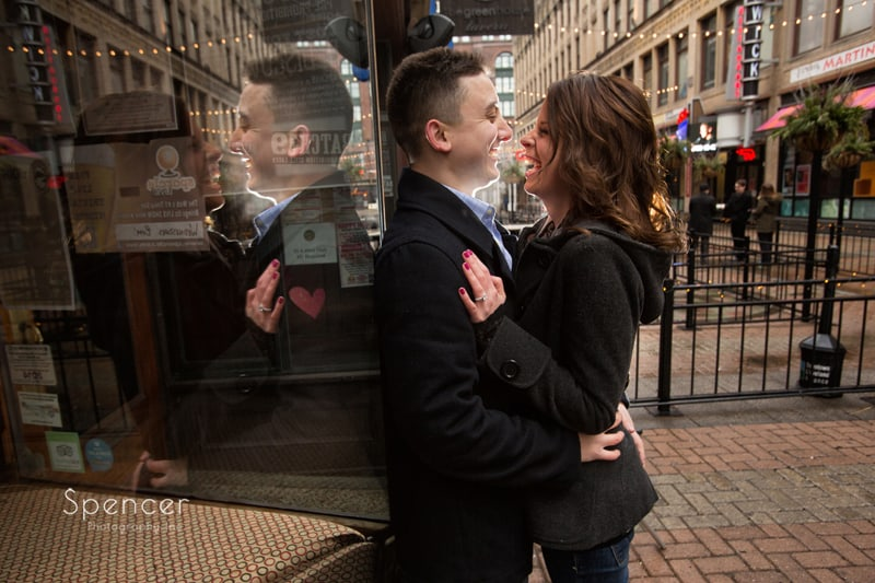 couple laughing in reflection on cleveland east fourth street engagement session