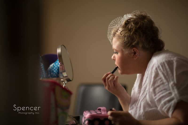 bride putting on lipstick before her akron wedding