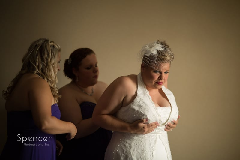 bride putting on wedding dress in akron hotel