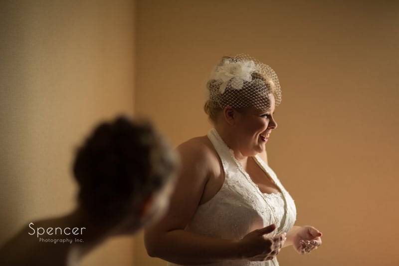 bride laughing after putting on her wedding dress