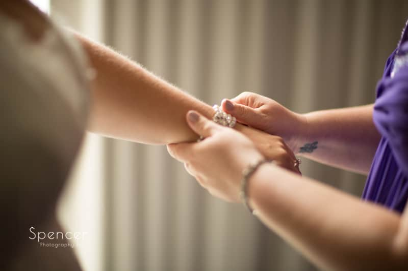 maid of honor helping bride with bracelet