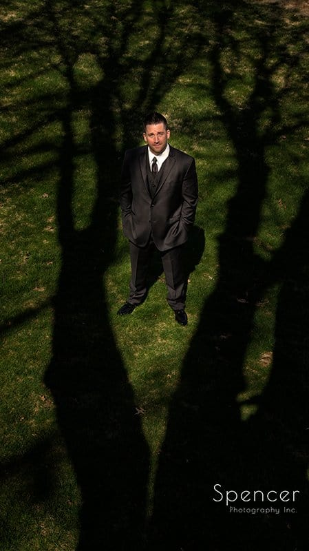 creative wedding picture of groom standing in shadow of tree