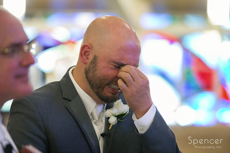 groom reacts to bride walking down wedding aisle at Holy Family Church