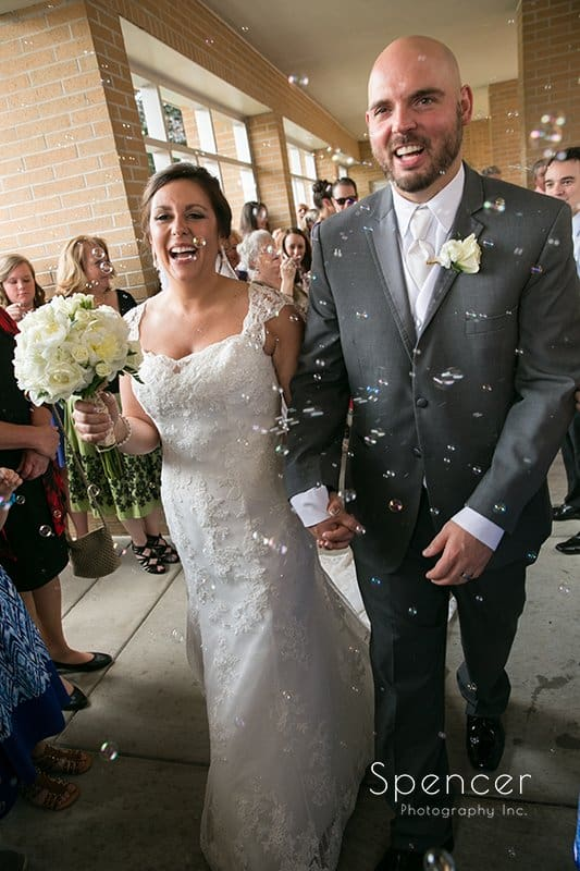 bride and groom exit Holy Family Church after their wedding ceremony