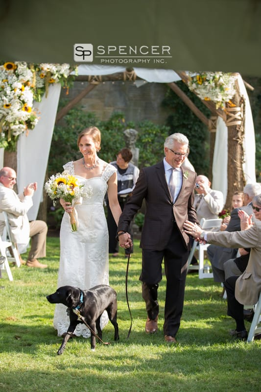 bride and groom walking down aisle with dog