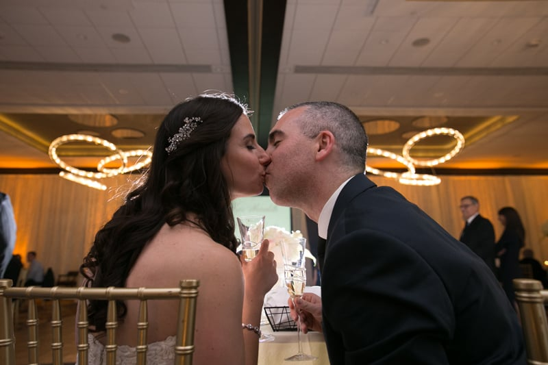 bride and groom kiss at their head table at westin