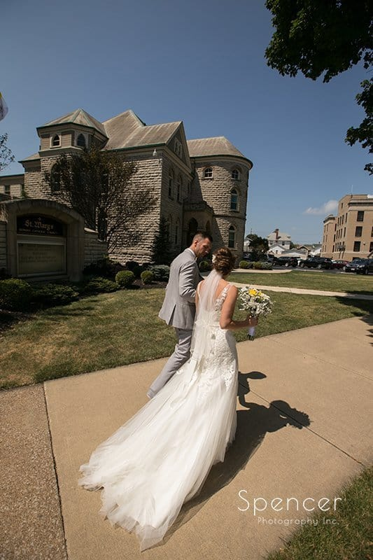 bride and groom walking past St. Mary's Catholic Church