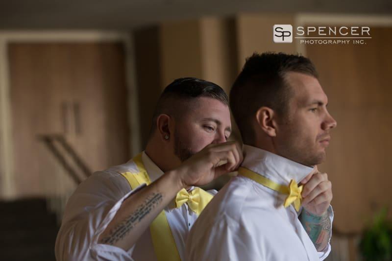 best man helping groom with tie