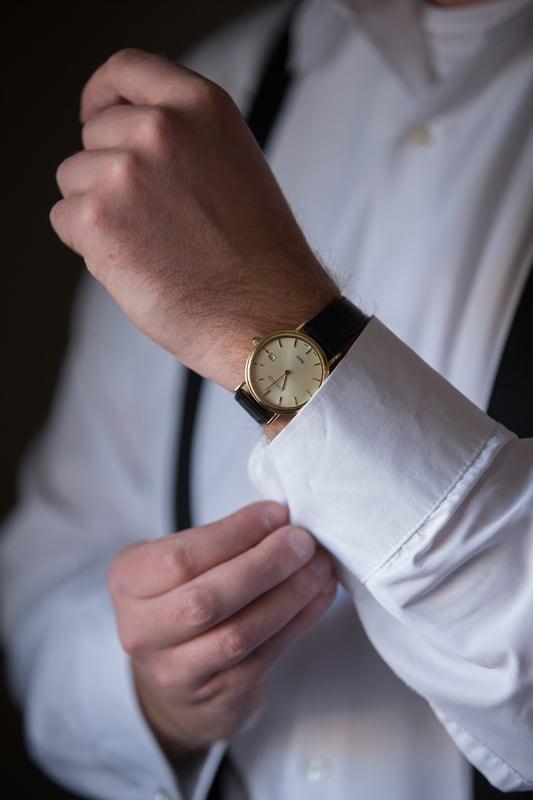 groom adjusting wedding cuff links at Wyndham Hotel